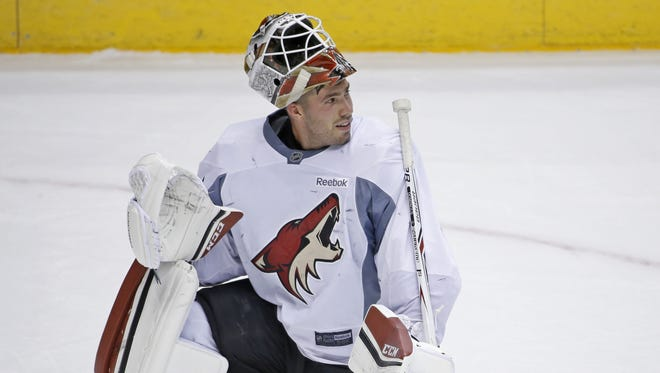 Coyotes' Louis Domingue talks with coaches during a practice at Gila River Arena on September 25, 2016 in Glendale, Ariz.