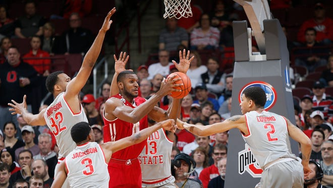 Wisconsin's Vitto Brown is smothered by a group of Ohio State defenders on Thursday night.