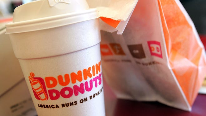 A cup of Dunkin' Donuts coffee and a donut bag sit on a counter September 7, 2006 in Chicago.