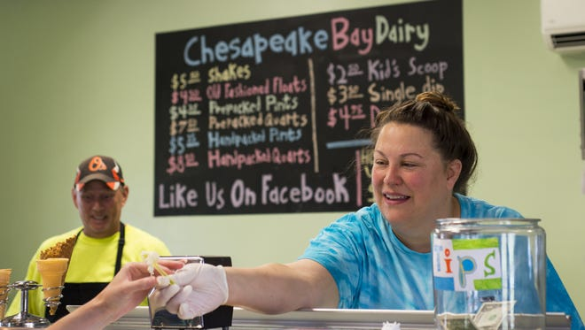 Laura Holland, owner of Chesapeake Bay Farms, serves a sample of one of the farm's 50 ice cream flavors.