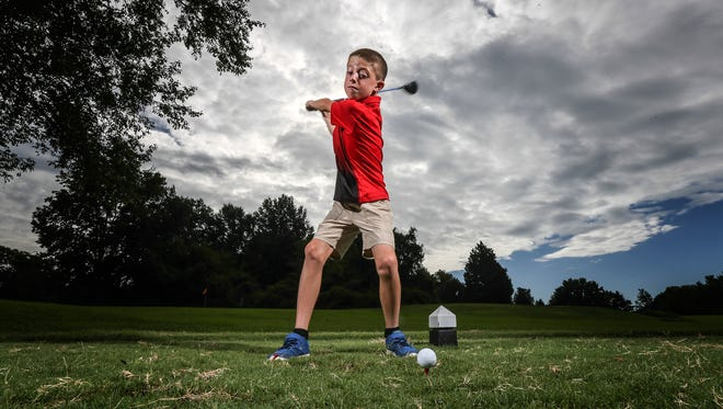 8-year old Luke Bryant takes a swing at the tee at the second hole of Woodhaven Country Club's 9-hole par 3 course. Luke got a hole-in-one at the hole in July.