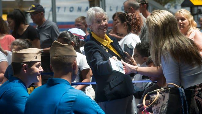 Sara Parkin, a volunteer at the National Naval Aviation Museum at Pensacola Naval Air Station, hands out souvenir pamphlets on April 19, 2017, to visitors during a Blue Angels autograph session at the museum.