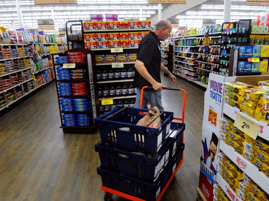 Pulling a cart loaded with groceries for the Streetside delivery service, Ralph Goode steers it through the United Supermarket's Market Street store Friday July 7, 2017. Outside, he loaded them into a delivery truck and brought them to customers as far as Tuscola and at various addresses around Abilene.