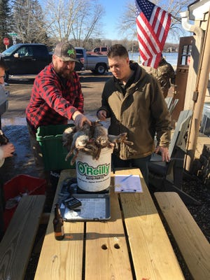 Shane Rockteacher (left) and Cody Kaiser weigh their rabbits outside the the Golden Lake Pub in Oconomowoc.