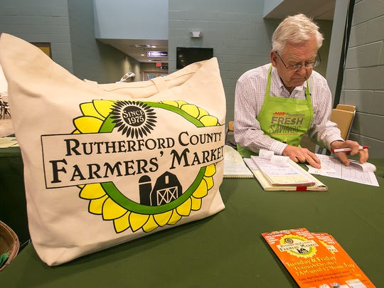 Joseph Smith goes over reciepts while he works the welcome desk at the Rutherford County Farmers Market.