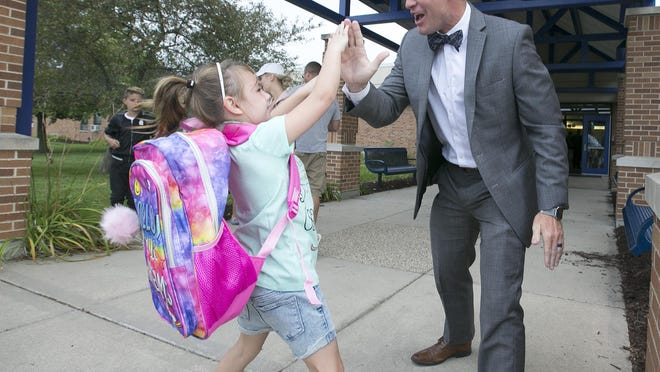 Ella Bilodeau, a kindergartner, gives Kevin Finnegan, Prairie Hill Elementary School principal, a high-five on Wednesday, Aug. 15, 2018, during the first day of school. The Prairie Hill School District is the only district in the region that is larger today than it was 10 years ago.