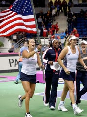 United States' CoCo Vandeweghe, 2nd right, and her teammates Shelby Rogers, left, celebrate Sloane Stephens, 2nd left, and Alison Riske, right, celebrate after defeating Belarus during the Fed Cup final match, in Minsk, Belarus, Sunday, Nov.12, 2017. United States defeated Belarus 3-2 and gained the Fed Cup title. (AP Photo/Sergei Grits)