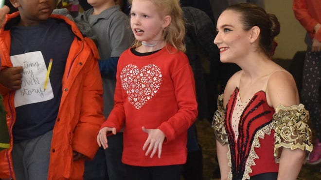 """A Savannah Ballet Theatre ballerina pauses to talk with students from the Matthew Reardon Center for Autism after a December low-sensory performance of """"The Nutcracker."""""""