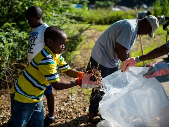 Tre'von Narcisse, 8, moves litter into a garbage bag while cleaning with members of Destiny of Faith Church near a cemetery on Martin Luther King Jr. Drive in Lafayette, La., Saturday, Sept. 19, 2015.