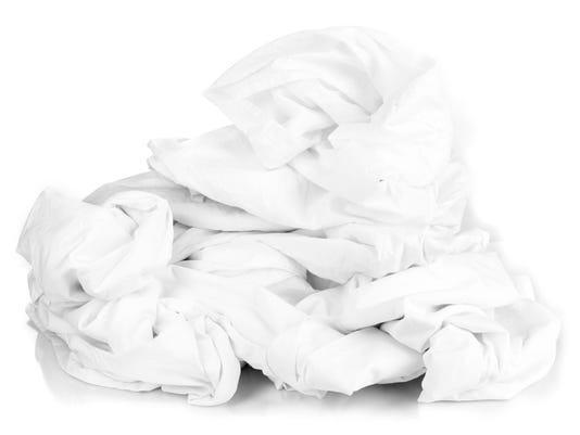 Rumpled bedding sheets isolated on white