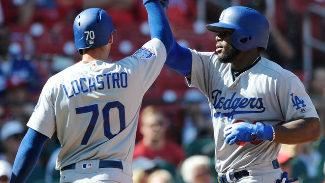 Los Angeles Dodgers' Tim Locastro (70) congratulates Yasiel Puig, right, after his three-run home run against the St. Louis Cardinals in the eighth inning of a baseball game, Saturday, Sept. 15, 2018, at Busch Stadium in St. Louis. (AP Photo/Bill Boyce)