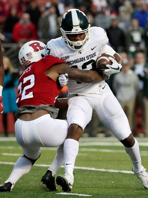 Michigan State wide receiver Laress Nelson is tackled by Rutgers defensive back Damon Hayes during the first half.