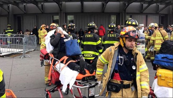 An injured passenger is taken from the Atlantic Terminal in Brooklyn after a Long Island Rail Road commuter train hit a bumping block,  Wednesday, Jan. 4, 2017.