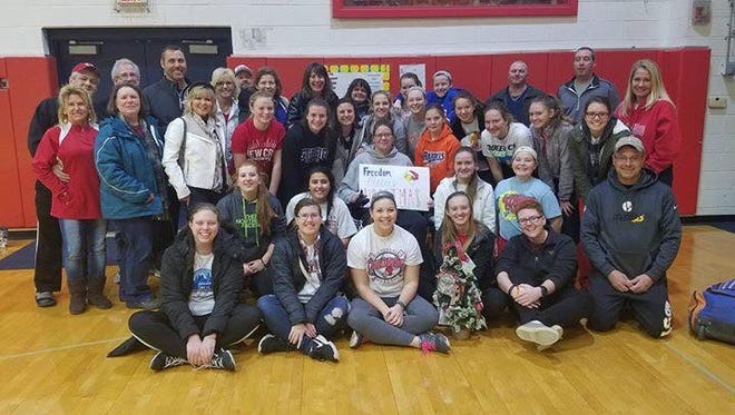 St. Henry coach Freedom Fogt is surrounded by some of the Crusaders softball family at an open gym in December.