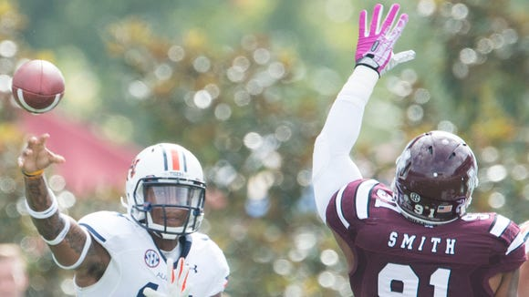 Auburn quarterback Nick Marshall throws a pass as Mississippi State defensive lineman Preston Smith puts his hand up during Saturday's game.