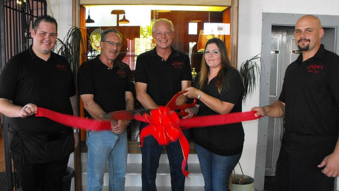 Marie Bennett cuts a Deming-Luna County Chamber of Commerce ribbon to her new business in a familiar setting at 101 S. Silver Avenue. Bennett has taken over her mother's restaurant and named it Marie's Italian Grill and Steak House. Along with her husband, Karl Bennett and her father Harold Richmond, and brother Bill Richmond, Marie says she is providing the same quality Italian cuisine and Angus steaks her mother, Palma, dished out.