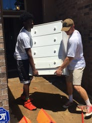 Comeaux High football players help clean up homes that