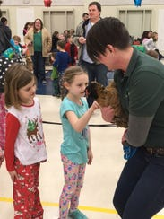 First grader Bailey Awe and Saylor Russell pet an animal
