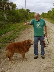 Bob Gore plays with his beloved golden retriever Cailin