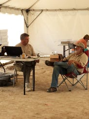 Dr. Doug Owsley, left, and Dan Griffith consult on