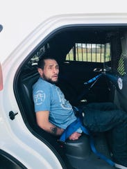 Jose Angel Baeza sits in a police car after being arrested