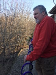 Ralph Amodeo stands overlooking the back of his home