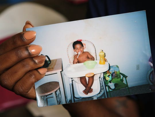 Ebony Dupont holds a picture of her son before he was