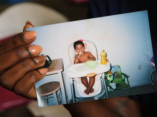 Ebony Dupont holds a picture of her son before he was taken to Puerto Rico by her finance, Omar Enrique Vidro Pacheco, who was later murdered during the visit. Vidro's mother took custody of the child in Puerto Rico and Dupont has been fighting in Delaware courts to get him back.