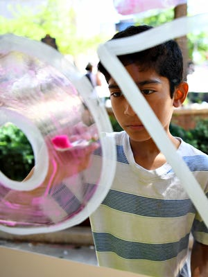 Jose Efpinoza, 11, paints a message of love for York City on PeoplesBank's window in Continental Square during the first week of the York City School District Police Department's SAFE Camp in York City, Thursday, July 12, 2018. Dawn J. Sagert
