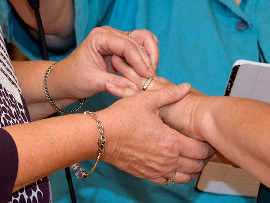 Karen Roberts, left, places a wedding band on the finger