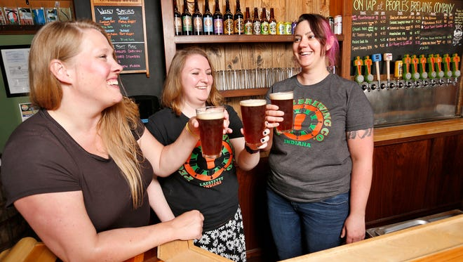 Jessica Johnson, from left, Sara Gertsch and Steph Silva enjoy a pint of Rosie the RIPA, a red India Pale Ale, Thursday, May 17, 2018, at People's Brewing Company, 2006 N. 9th Street in Lafayette. The women brewed the IPA in honor of International Women's Day. The beer will be available at 3 p.m. Saturday in People's tap room.