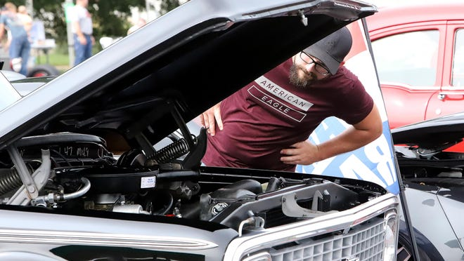 Charles Williams looks over Tony Jones' 1972 Chevy C 10 entered in the Hiller family benefit car show, Saturday, Sept. 12, in Lavaca.