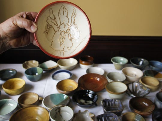 """Tina Oxer, of East Lansing, a member of the Greater Lansing Potter's Guild, shows a piece of handcrafted pottery a member of her guild made to help raise money for the Greater Lansing Food Bank, Thursday, October 2, 2014, during the 24th annual """"Empty Bowls"""" fundraiser at Troppo in downtown Lansing.  Attendees donated $20/piece"""