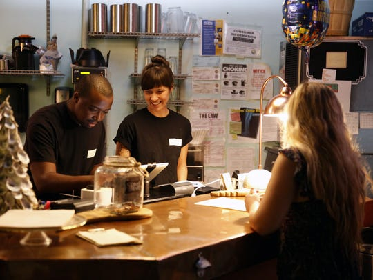 Kevin Graham, left, and Sophia Parker, help a customer