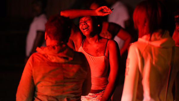 A young woman mourns Thursday, Aug. 20, 2015, at the scene of the shootings at a Boys and Girls Club in Rochester, N.Y., on Wednesday, Aug. 19, 2015. Three people were killed after seven were shot.