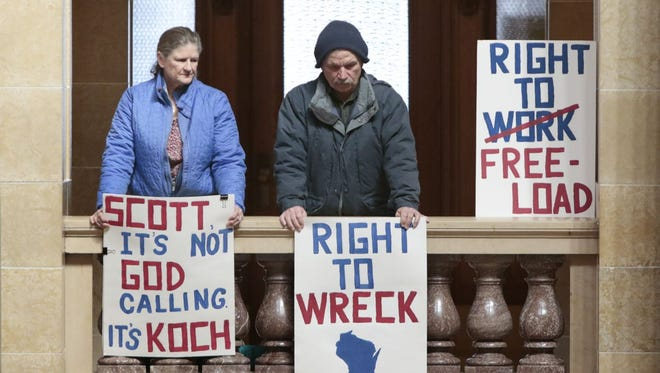 Opponents of Right to Work legislation hold signs in an upper level of the State Capitol in Madison, Wis., Monday, March 2, 2015.
