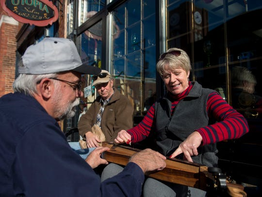 Tony Weis teaches Elise Lawrence-Mundy to play an Appalachian Mountain dulcimer outside of the Creation Station during Christmas in New Harmony in downtown New Harmony, Ind., on Saturday, Dec. 2, 2017. The annual event included a craft market, musical performances, open houses at local merchants, and photos with Santa.