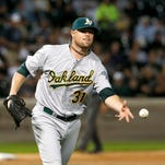 Oakland Athletics pitcher Jon Lester tosses the ball to first baseman Nate Freiman against the Chicago White Sox on Sept. 9, 2014.