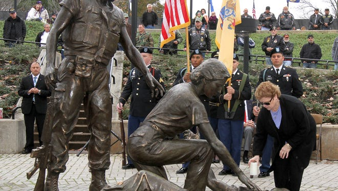 """Elizabeth Burns, Spring Lake Heights, leaves a candle next to the statues inside the New Jersey Vietnam Veterans' Memorial during the """"in Memory"""" portion of the Veterans Day Ceremony in Holmdel Wednesday, November 11, 2015.  Burns' husband James was recognized during the ceremony."""