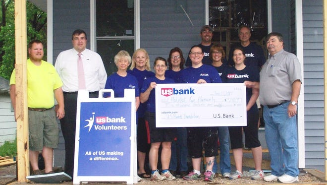 Representatives from Habitat for Humanity and U.S. Bank pose for a photo. Left to right: Joel Boelhower, HFH Construction manager; Branch Manager Andrew Dengel, Kris Tatros, Melanie Fox, Judy Reams, Teri Small, Stacy Bonincontri, Tim Muellenbach, Patti Schumacher, Elizabeth Winske, Gary Ott and Tom Wilhelms, HFH executive director.