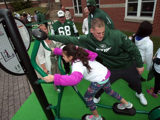 New York Jets FB/LB Julian Howsare helped out Catalina Fernandez on the elliptical machine Howsare and other members of the New York Jets unveil a PLAY 60 Fitness Zone playground with 35 students from Dover Middle School as part of the NFLÕs 17th annual Hometown Huddle, an NFL-wide day of service with United Ways across the nation. October 20, 2015, Dover, NJ