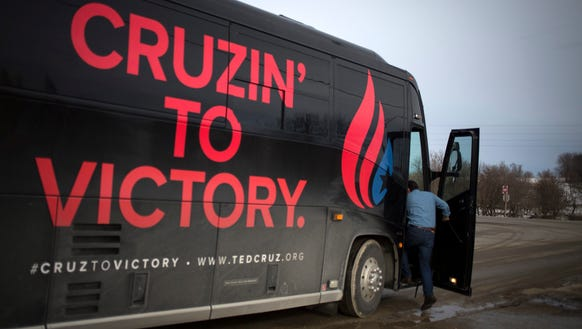 Ted Cruz boards his campaign bus after an event at