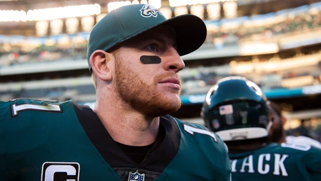 Eagles quarterback Carson Wentz takes the field to greet players after a 31-3 win over the Bears Sunday, Nov. 26, 2017 in Philadelphia.