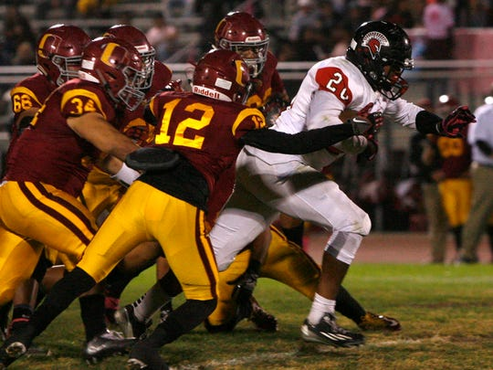 Rio Mesa High's Dondre Baker (right) breaks loose of a swarm of Oxnard defenders during Friday night's Pacific View League showdown,