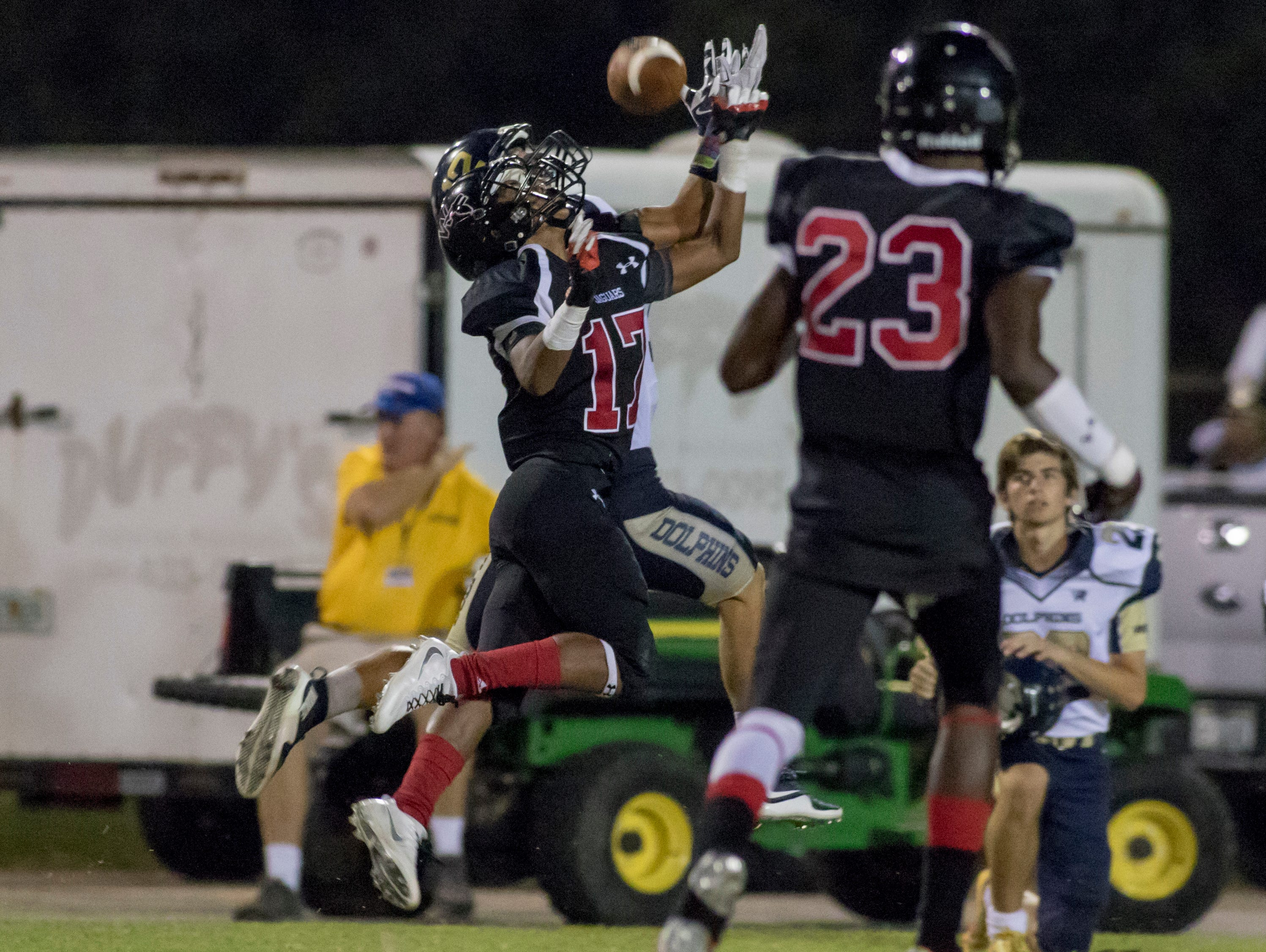 West Florida's Da'Quaris Gaines (23) looks on as his teammate (17) and Gulf Breeze wide receiver Cole Sheppard (12) leap for a pass during a Sept. 23 matchup.