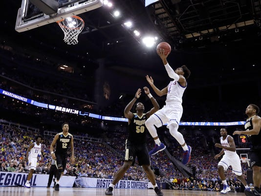 Kansas guard Devonte' Graham drives to the basket in front of Purdue forward Caleb Swanigan (50) during the first half of a regional semifinal of the NCAA men's college basketball tournament, Thursday, March 23, 2017, in Kansas City, Mo. (AP Photo/Charlie Riedel)