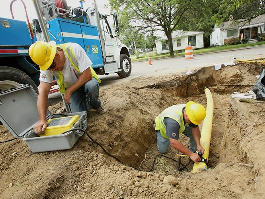 Two Consumers Energy employees replace underground gas pipeline near Flint in July 2013.