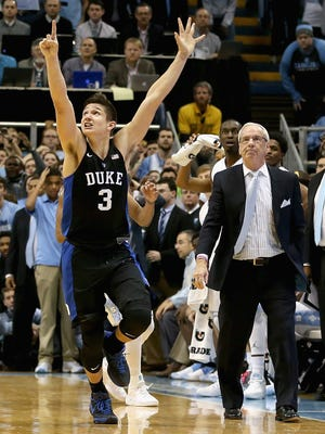 Grayson Allen of the Duke Blue Devils celebrates after defeating the North Carolina Tar Heels 74-73 as head coach Roy Williams watches on during their game at Dean Smith Center.