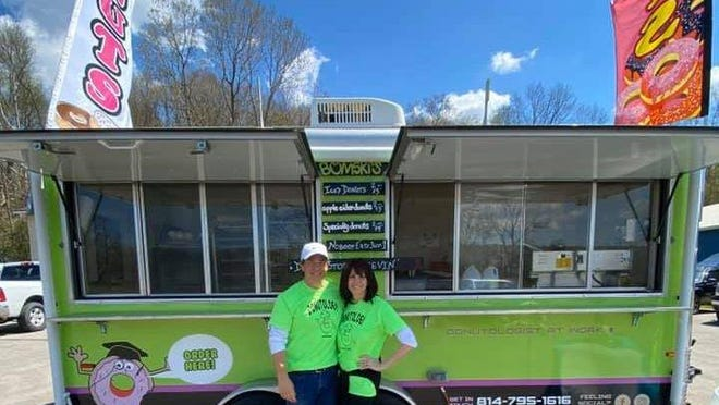 David and Melissa Fink pose in front of Donutology, a Meadville food truck, on opening day.