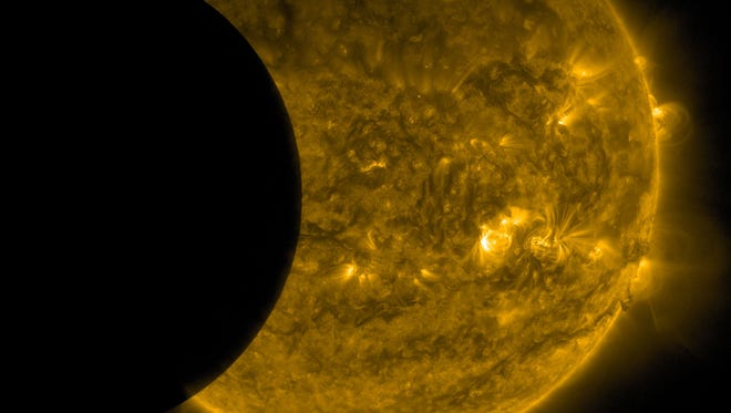 This Sept. 13, 2015, image provided by NASA shows the moon, left, and the Earth, top, transiting the sun together, seen from the Solar Dynamics Observatory. The edge of Earth appears fuzzy because the atmosphere blocks different amounts of light at different altitudes. This image was taken in extreme ultraviolet wavelengths, invisible to human eyes, but here colorized in gold. A total lunar eclipse will share the stage with a so-called supermoon Sunday evening, Sept. 27, 2015, as seen from the United States. That combination hasn't been seen since 1982 and won't happen again until 2033.